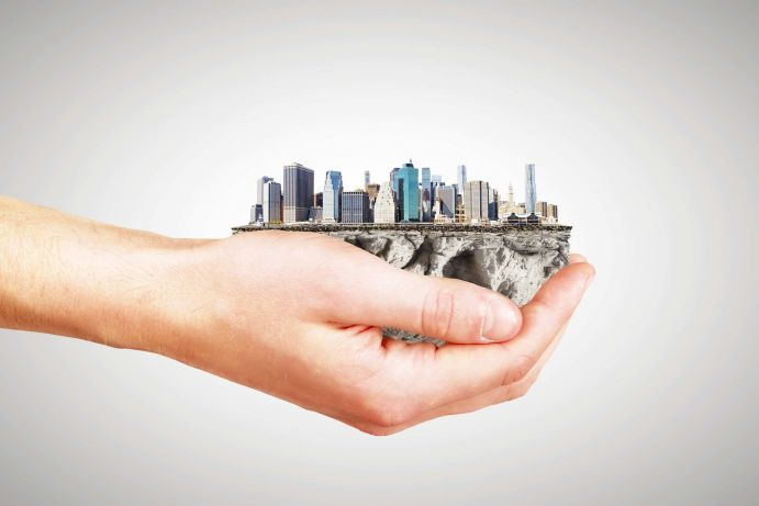 Whole world in one hand concept with man hand and part of megacity