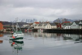 A local fishing vessel is leaving its home port on the Lofoten. Lofoten is known for a distinctive scenery with dramatic mountains and peaks, open sea and sheltered bays, beaches and untouched lands. Though lying within the Arctic Circle, the archipelago experiences one of the world's largest elevated temperature anomalies relative to its high latitude.