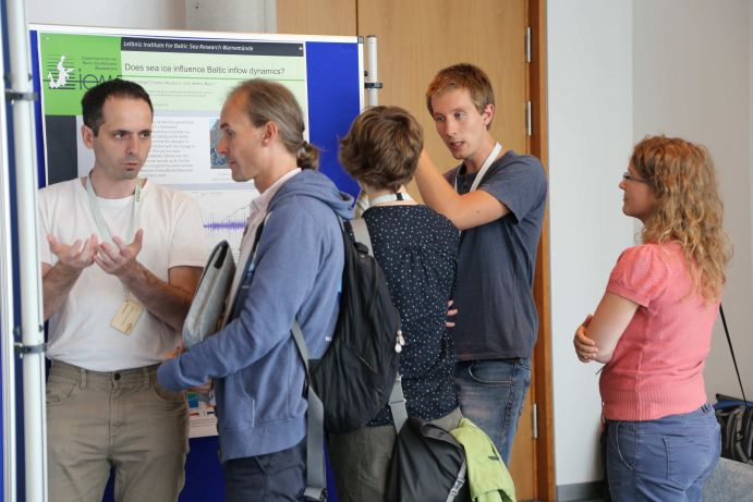 Scientists discuss their finding in a poster session.