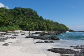 A person walks along a beach featuring some rocky outcrops. A tropical forest stretches along the background.